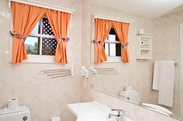 Декорирование окна в ванной при помощи занавески