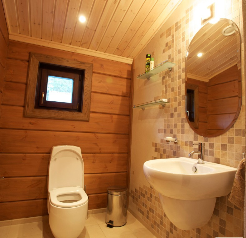 Туалет в деревянном доме с окном