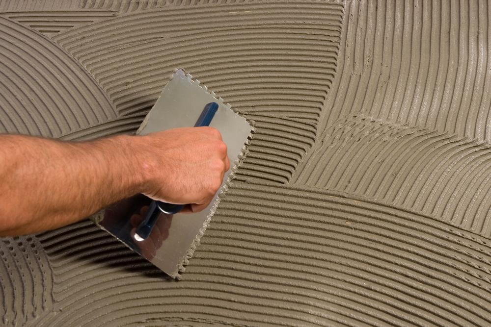 Нанесение плиточного клея перед укладкой плитки