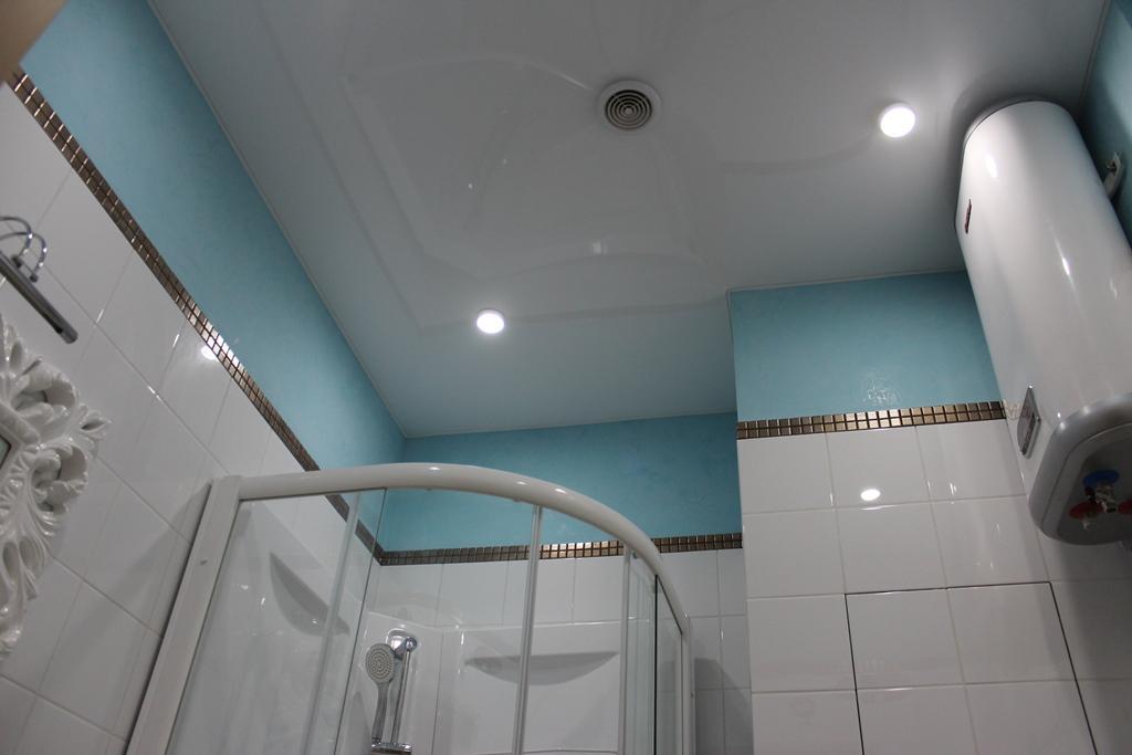 Белый натяжной потолок отлично дополняет белую плитку