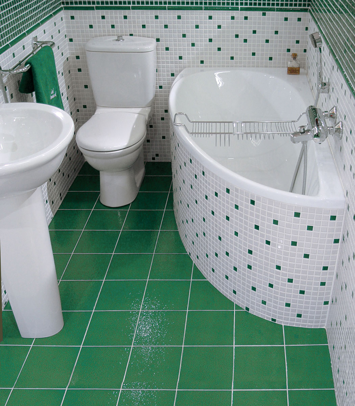 Зеленая плитка на полу в ванной