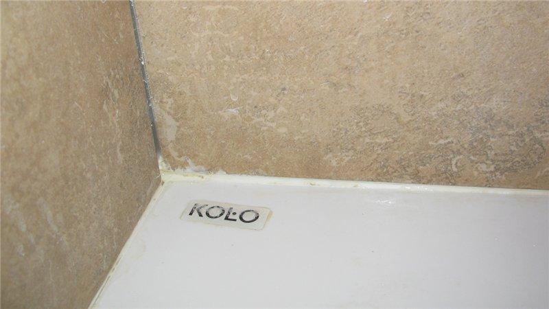 Очищаем стык между ванной и стеной