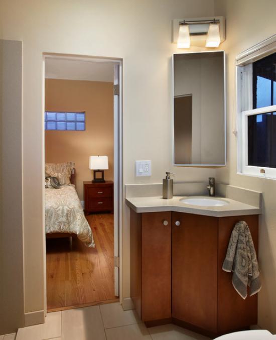 Коричневая тумба в угол с цоколем в интерьере ванной комнаты с встроенной в нее тумбой