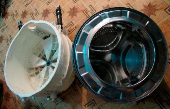 Из стиральной машинки вынимают бак